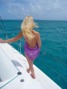 picture of woman with blonde hair on sailboat catamaran caribbbean sea blue ocean a vacation state of mind jaye frances www.jayefrances.com